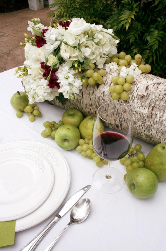 Kwiaty, jabłka i winogrona jako dekoracje stołów weselnych