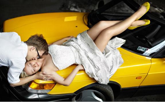 Para Młoda pozuje na żółtym samochodzie