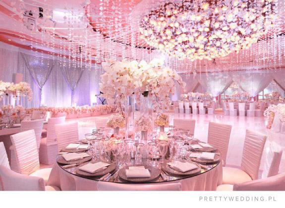 Ogromne dekoracje z białcych kwiatów przy suficie i na okrągłych stołach