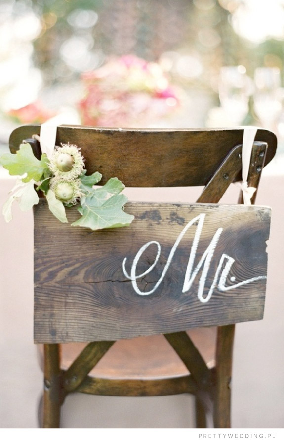 Dekoracja krzesełek na weselu z wykorzystaniem żołedzi i drewnianej tabliczki