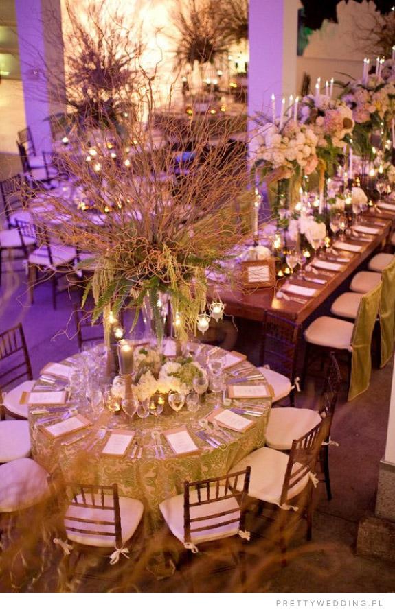 Aranżacja okrągłych stołów ślubnych z gałęzi i kwiatów