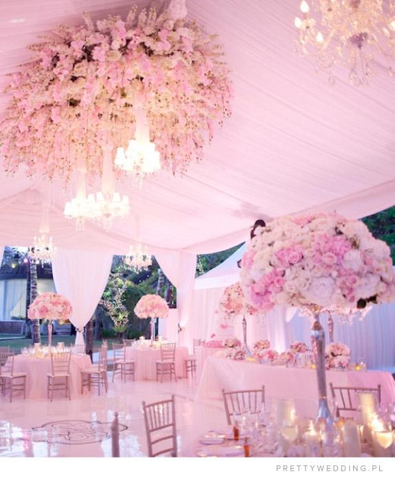 Olbrzymi dekoracje kwiatowe w sali weselnej na stołach i na suficie